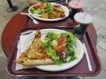 Tarjottimella pitsa, salaatti ja juoma sekä toisella tarjottimella neljä käärylettä, salaatti ja juoma.