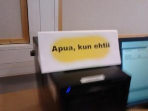 """jonotuskolmio tietokoneen keskusyksikön päällä. Esillä keltataustainen sivu tekstillä """"Apua, kun ehtii"""""""